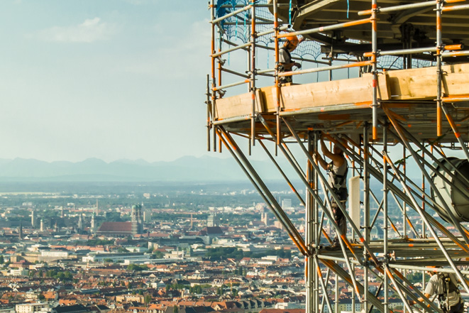 Luftaufnahme vom Gerüst am Olympiaturm in München, im Hintergrund die Frauenkirche
