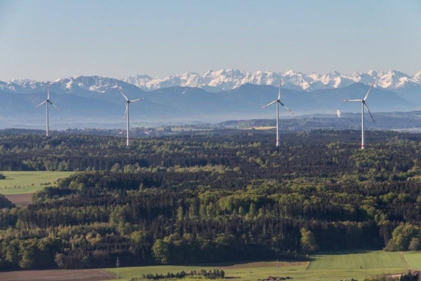 Foto aus der Luft von einem Windpark in Südbayern, im Hintergrund die Alpen